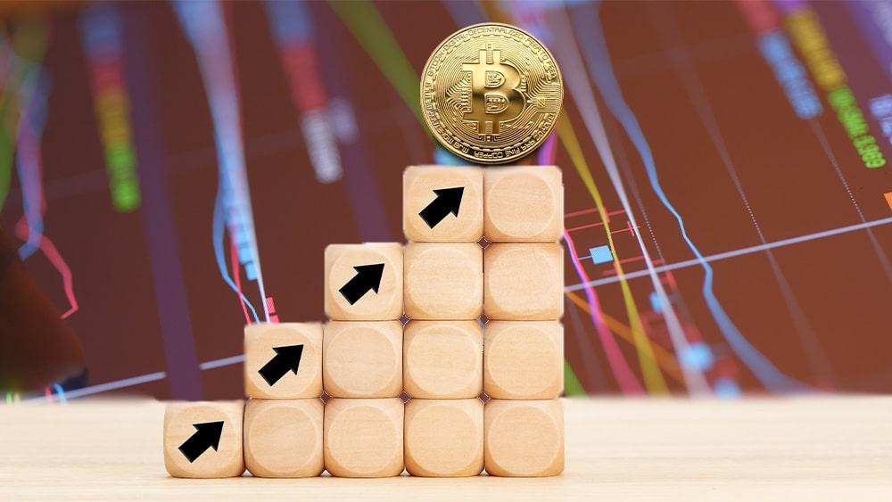 Bitcoin sobre bloques de madera con flechas hacia arriba.