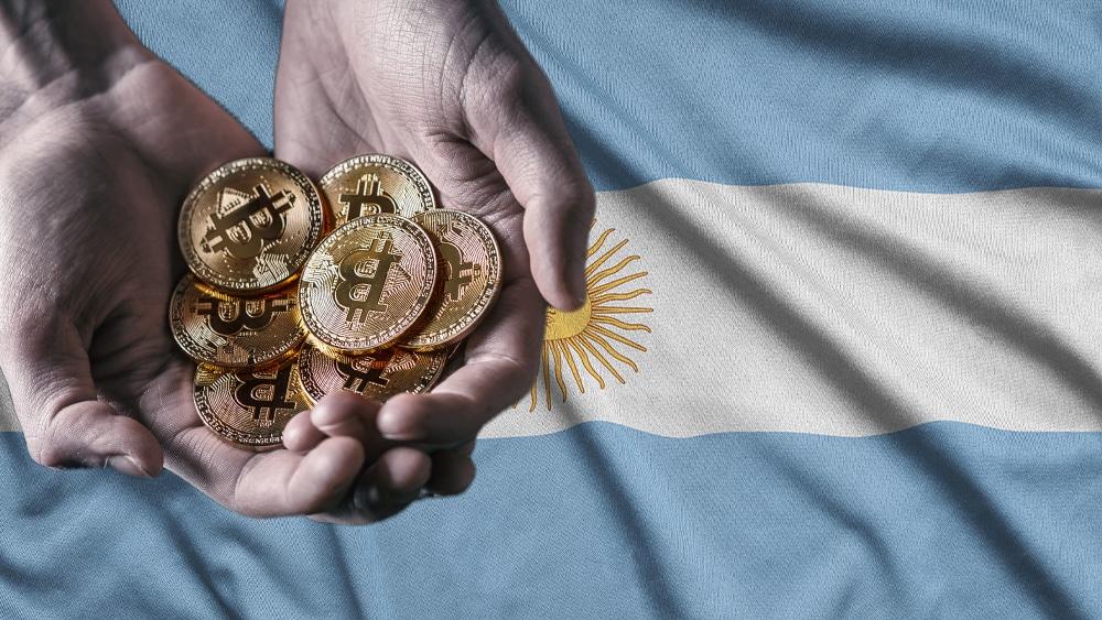 Bandera de Argentina y y mano sosteniendo bitcoins.