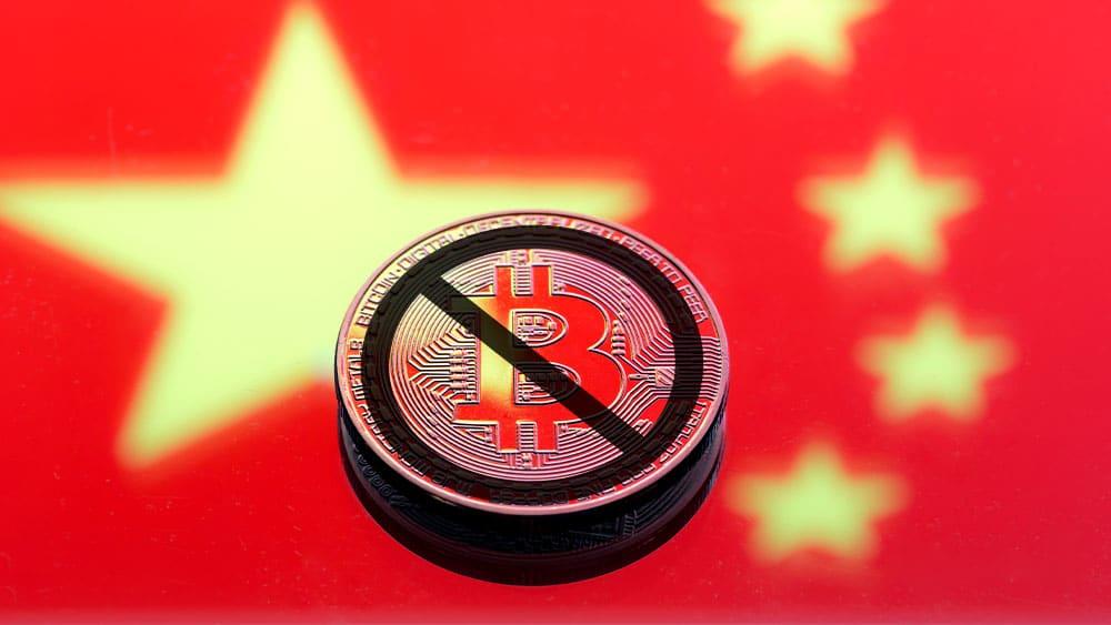 Bandera de China con bitcoin tachada como prohibida.