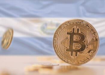 Bitcoins sobre mesa y bandera de El Salvador.