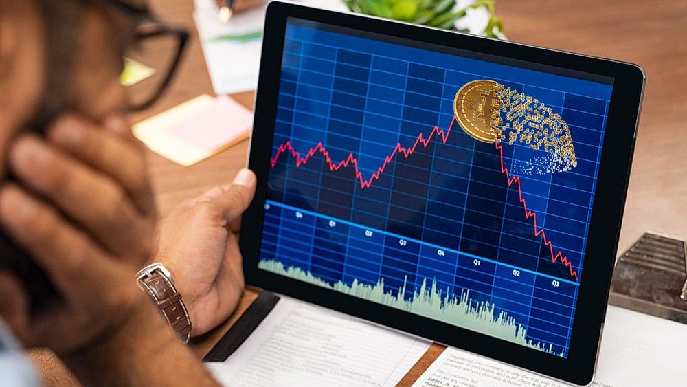 Persona y gráfico bursátil con bitcoin en la cima.