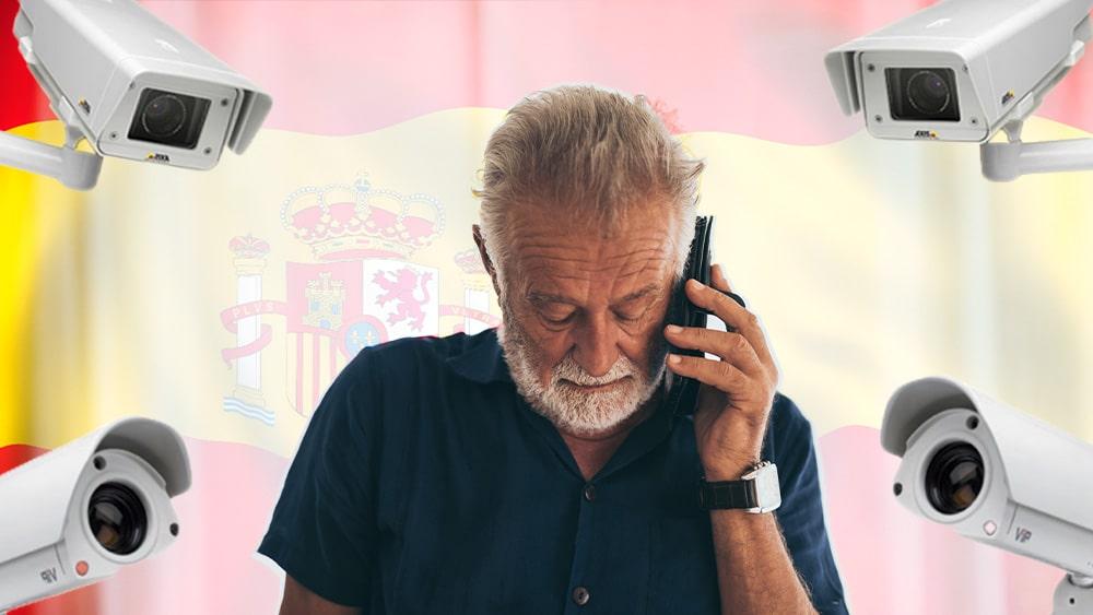 Hombre habla por teléfono con bandera de España y cámaras de vigilancia.