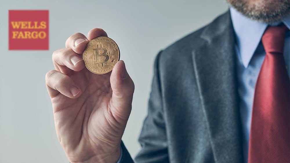 Hombre de negocios con bitcoin en mano y logo de Wells Fargo al fondo.