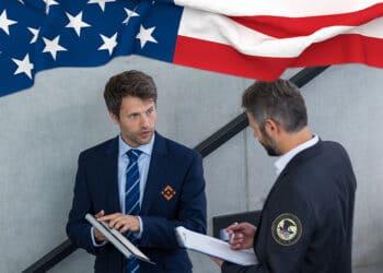 Funcionario del departamento de justicia y de Binance conversando sobre bandera de USA.