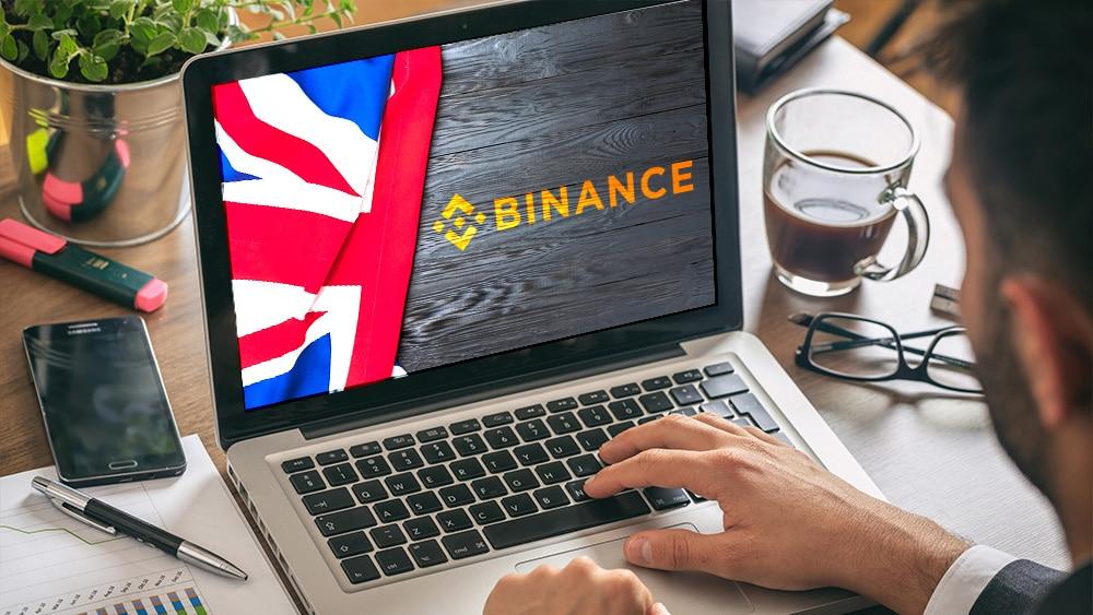 Laptop con logo de Binance y bandera de Reino Unido.