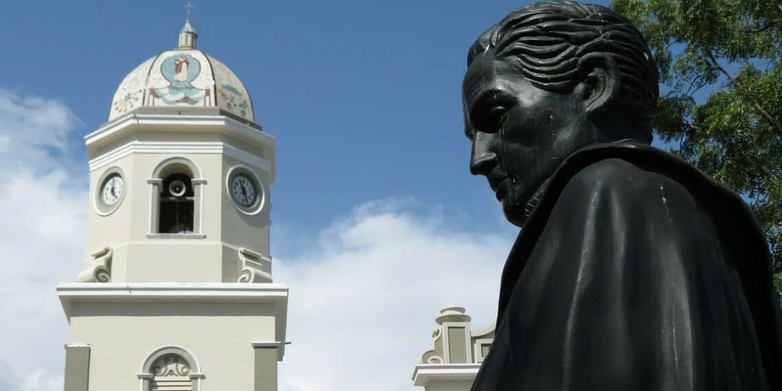 Busto de Simón Bolívar con campanario detrás.