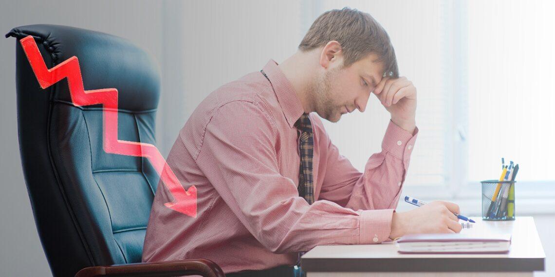 Hombre sentado en butaca de oficina preocupado por mercado bajista