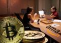 Mesa con logo Amazon y personas conversando, BTC en primer plano.