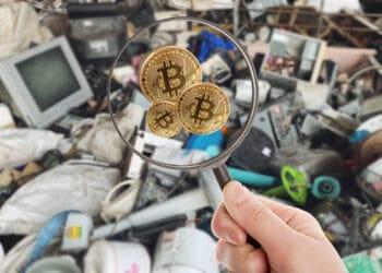 Basurero y lupa buscando bitcoins.