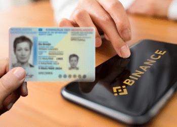 Teléfono con logo de Binance y mano sosteniendo identificación personal.
