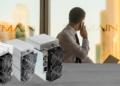 Persona en oficina con logo de Bitmain y varios Antminer sobre mesa.