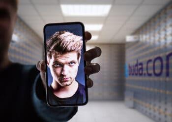 Persona mostrando selfie en teléfono y logo de buda.