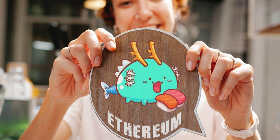 Persona sosteniendo token de axie con letras ethereum.