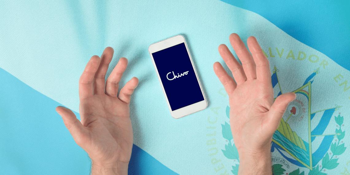 Manos reclamando a un teléfono con logo de Chivo Wallet y bandera de El Salvador de fondo.