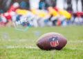 NFT y balón de fútbol con logo de NFL.