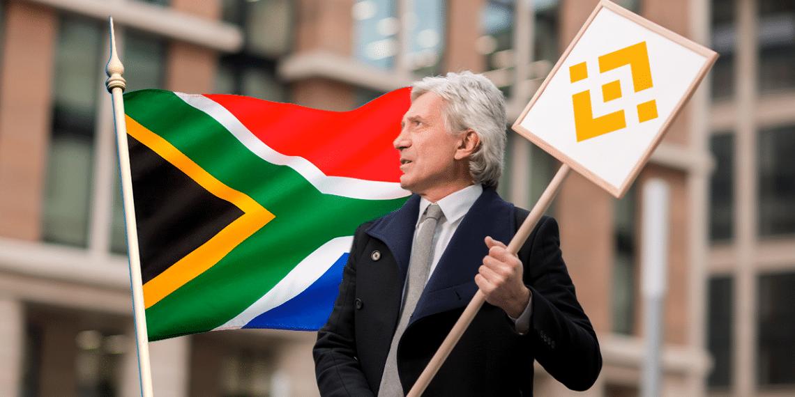 Señor con cartel de Binance y bandera de Sudáfrica.