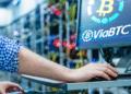 Persona en granja de BTC frente a pantalla con logo de ViaBTC.